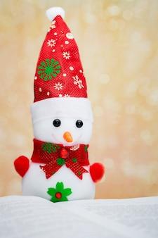 Um boneco de neve em um livro aberto. lendo livros favoritos. ano novo e presentes de natal_