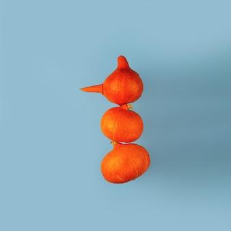 Um boneco de neve feito de abóboras com nariz de cenoura