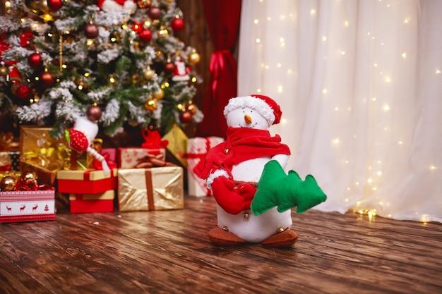 Um boneco de neve segurando uma árvore de natal