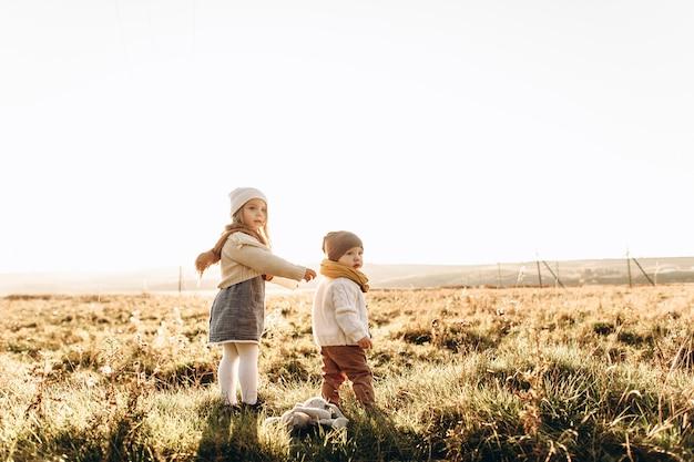 Um bonito crianças estão brincando no campo verde ao pôr do sol