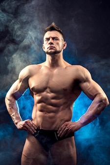 Um bonito jovem forte sexual com corpo musculoso, segurando a corda