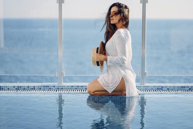 Um, bonito, menina jovem, com, um, chapéu palha, sentando, ligado, um, verão, terraço, por, a, piscina