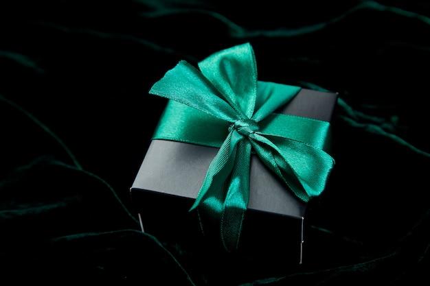 Um boxe de presente preto de luxo com fita esmeralda
