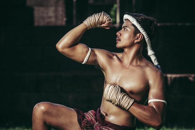Um boxeador amarrou uma corda na mão e realizou uma luta, as artes marciais do muay thai.
