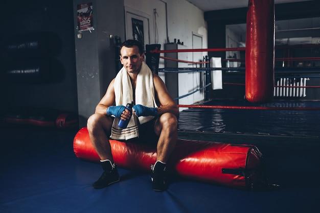 Um boxeador bebe água enquanto treina em uma academia