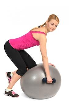 Um braço-haltere row no exercício de bola de aptidão de estabilidade