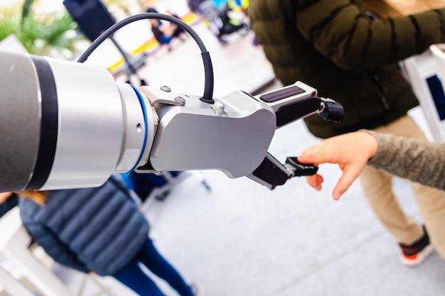 Um braço robótico brincou com uma criança em uma exposição inovadora de engenharia e indústria.