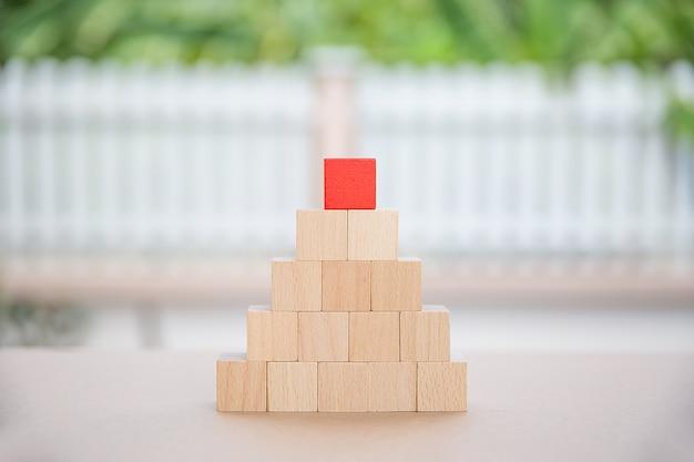 Um brinquedo de madeira do bloco da forma do cubo empilhado na forma da pirâmide sem gráfico.