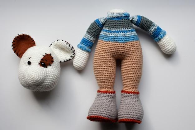 Um brinquedo de rato de crochê inacabado. cabeça separada do corpo.
