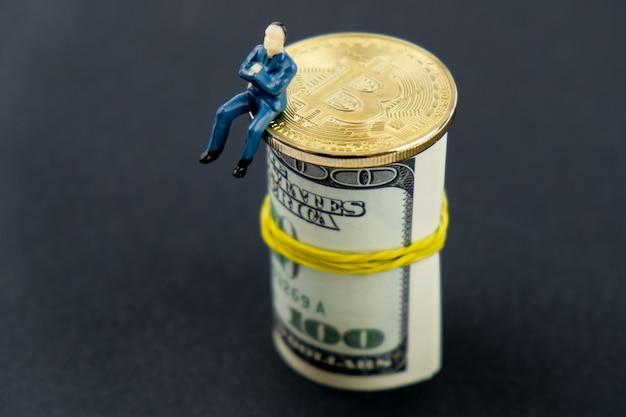 Um brinquedo do modelo do homem senta-se em uma moeda do bitcoin e em um rolo de notas dos dólares americanos.
