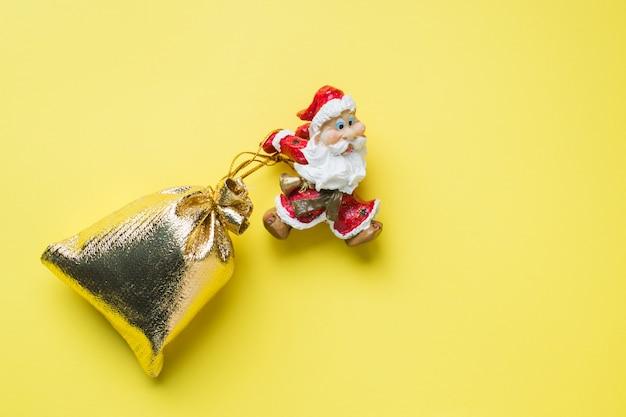 Um brinquedo santa com um saco de ouro de presentes em fundo amarelo, com espaço de cópia. o conceito de ano novo de natal.