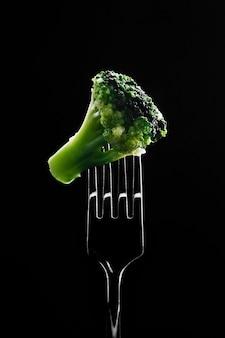 Um brócolis verde e um garfo de aço em um fundo escuro