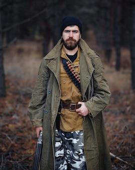 Um brutal caçador furtivo barbudo com um chapéu preto e uma jaqueta cáqui e uma capa longa segura uma arma na mão contra o fundo