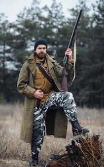 Um brutal caçador furtivo barbudo com um chapéu preto e uma jaqueta cáqui e uma capa longa segura uma arma, uma grande faca de caça e coloca o pé em um toco