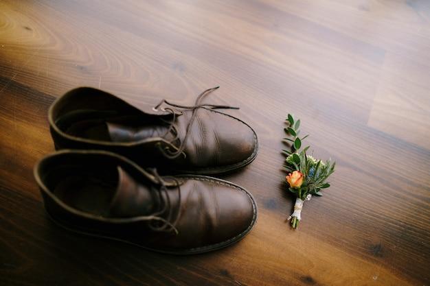 Um budier com uma rosa para o noivo e sapatos masculinos