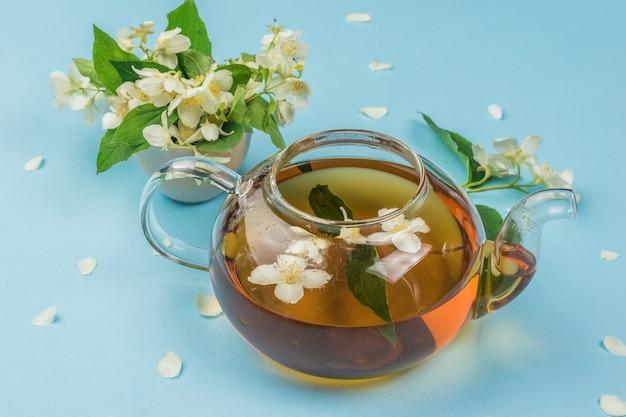 Um bule aberto com chá floral em um fundo azul. uma bebida revigorante que faz bem à saúde.
