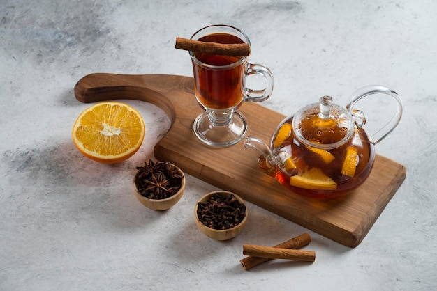 Um bule com chá e uma fatia de laranja na placa de madeira.