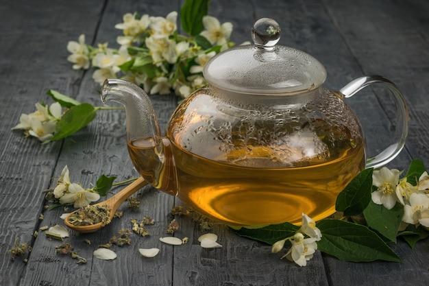 Um bule de chá de jasmim de vidro sobre uma mesa de madeira preta. uma bebida revigorante que faz bem à saúde.