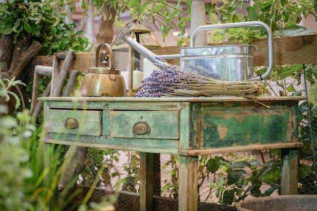 Um bule de chaleira, regador e flores de lavanda na mesa verde de madeira de estilo antigo. cottage jardim ao ar livre rústico.