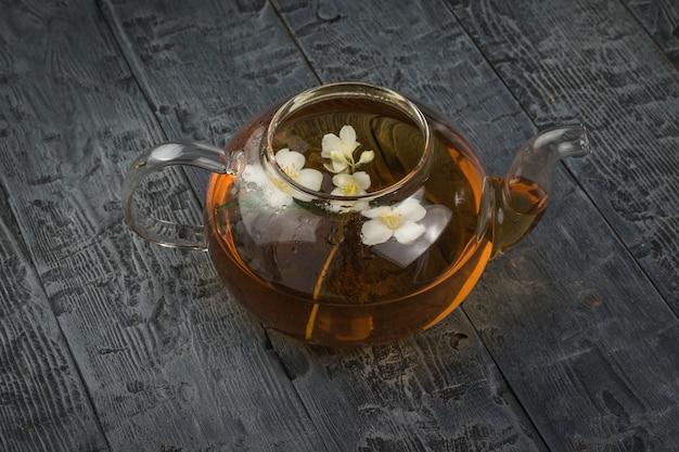 Um bule de vidro aberto com pétalas de jasmim e chá de flores sobre uma mesa de madeira.