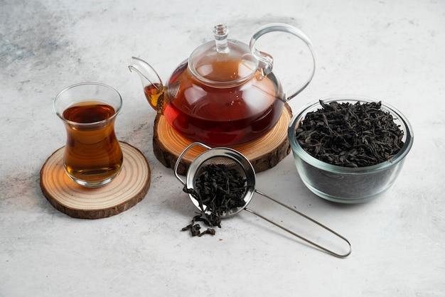 Um bule de vidro com chá na placa de madeira.