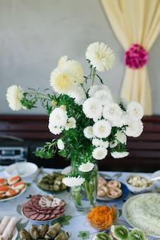 Um buquê de ásteres caseiros em um vaso de vidro na decoração de um banquete country