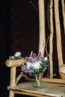 Um buquê de casamento de primavera de rosas lilás e brancas encontra-se em uma cadeira de madeira decorativa. buquê de casamento, detalhes, casamento, decoração.