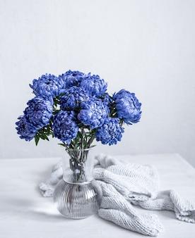 Um buquê de crisântemos azuis em um vaso de vidro e um elemento de malha em um fundo branco, copie o espaço.