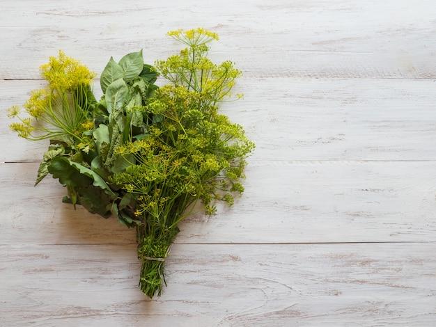 Um buquê de especiarias para decapagem. especiarias verdes para preservar legumes em um fundo branco de madeira