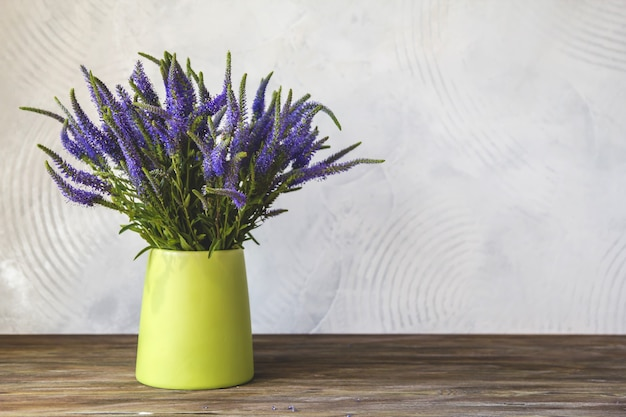 Um buquê de flores azuis de verônica em um vaso verde