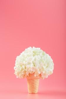 Um buquê de flores brancas em uma casquinha de sorvete em uma parede rosa.