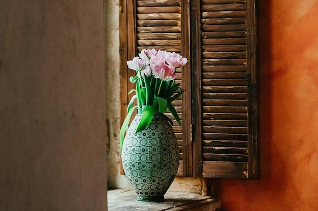 Um buquê de flores com foco suave em um vaso no peitoril da janela