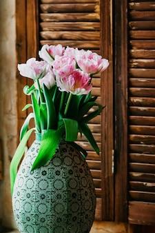 Um buquê de flores com foco suave em um vaso velho