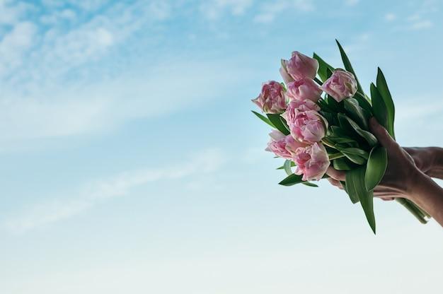 Um buquê de flores cor de rosa em uma mão contra o fundo do céu azul