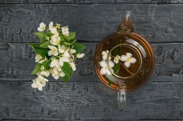 Um buquê de flores de jasmim e um bule com chá floral em um fundo de madeira.