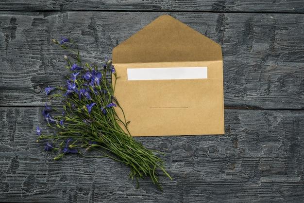 Um buquê de flores e um envelope aberto em uma mesa de madeira. postura plana.