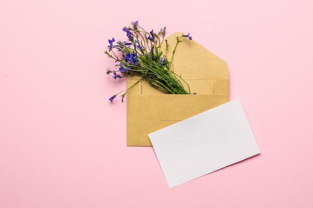 Um buquê de flores em um envelope e uma folha de papel branco sobre um fundo rosa. postura plana.