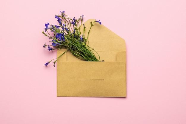 Um buquê de flores em um envelope postal de papel em um fundo rosa. postura plana.