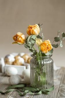 Um buquê de flores em um vaso de vidro com elementos decorativos em um fundo desfocado. conceito de férias da páscoa.