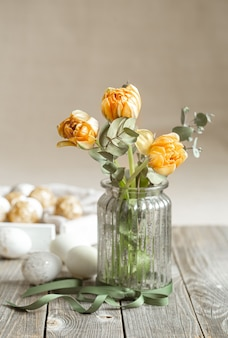 Um buquê de flores em um vaso de vidro com elementos decorativos em uma parede borrada. conceito de férias da páscoa.