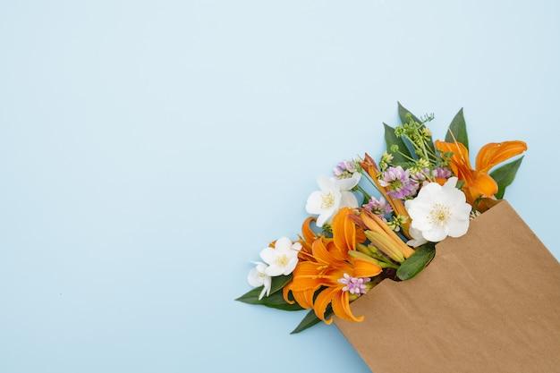 Um buquê de flores em uma bolsa de artesanato em um fundo azul