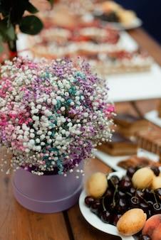 Um buquê de flores fofo em uma caixa redonda sobre uma mesa festiva.