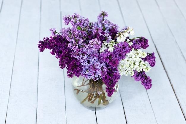 Um buquê de flores lilás frescas em um vaso de vidro no chão de madeira.