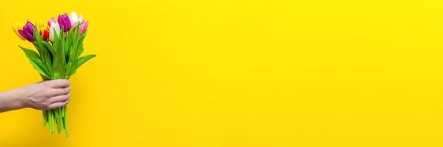 Um buquê de flores na mão de um homem em uma parede amarela
