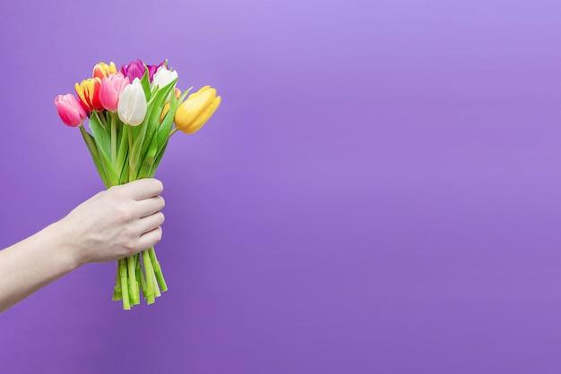 Um buquê de flores na mão de um homem em uma parede roxa