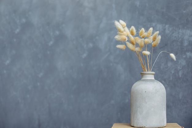 Um buquê de flores secas em um vaso de cerâmico branco, sobre um fundo cinza-azul.
