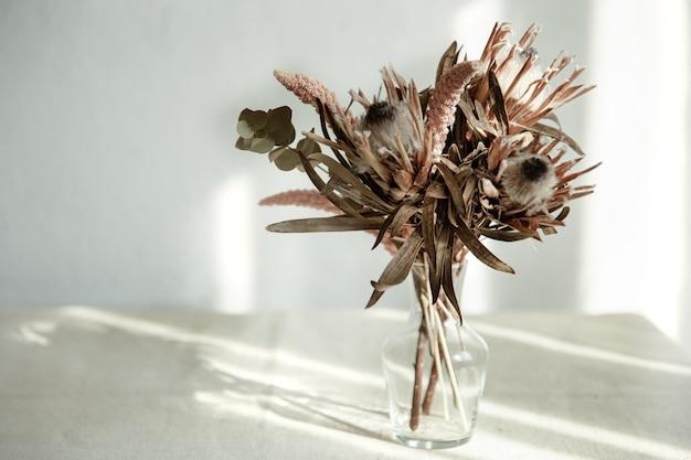 Um buquê de flores secas em um vaso de vidro sobre um fundo claro com luz solar.