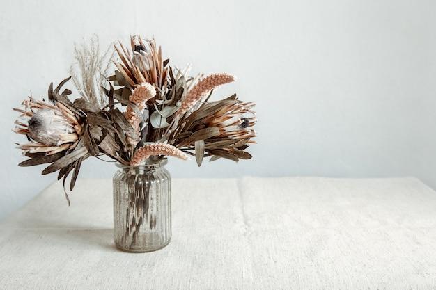 Um buquê de flores secas em um vaso de vidro sobre um fundo claro