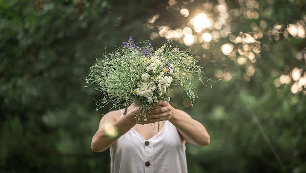Um buquê de flores silvestres nas mãos de uma garota em um fundo desfocado na floresta.