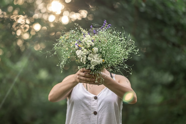 Um buquê de flores silvestres nas mãos de uma garota na floresta.